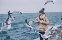 Portrait Of Young Happy Woman Feeds Seagulls On The Sea. Pretty Female Wearing Coat, Scarf, Hat Watching Flying Seagulls By The Sea On Cold Season. People And Nature Concept.