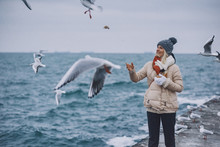 Happy Young Woman Tourist Feeds Seagulls On The Sea. Pretty Female Wearing Coat, Scarf, Hat Watching Flying Seagulls By The Sea On Cold Season. People, Travel, Environment And Nature Concept.