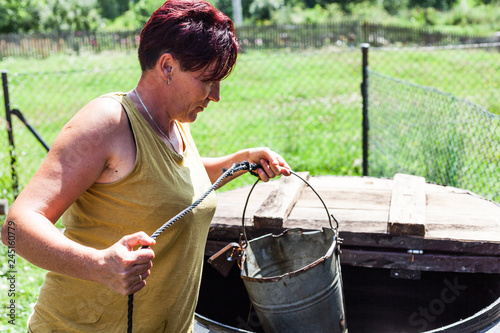 View of a hardworking mother holding a metal bucket with a string attached Fototapeta
