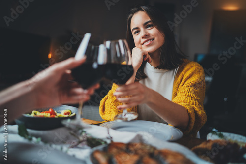 Fototapeta Romantic couple dating at night in restaurant, cozy atmosphere, beautiful young couple making cheers with glasses of red wine during romantic dinner, Sweet Couple Date Dinner obraz
