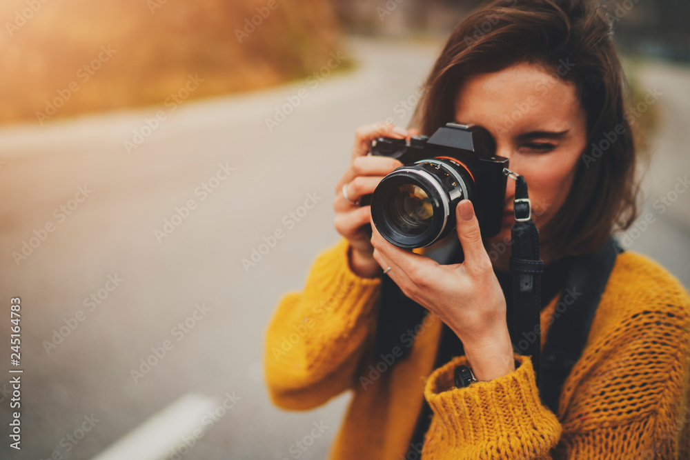 Fototapety, obrazy: Young female photographer taking photograph on vintage camera outdoors, blank space for text message or design, tourist girl enjoying road trip in Europe, flare light