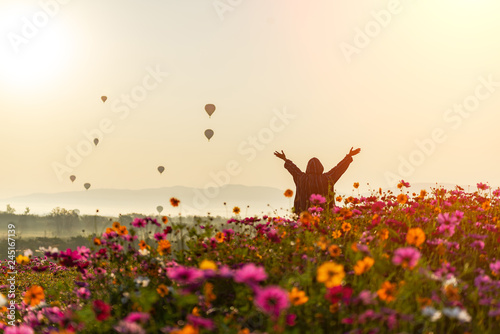 Fotografia  Lifestyle traveler women raise hand feeling good relax and happy freedom and see the fire balloon outdoors the nature tea and cosmos farm in the sunrise morning