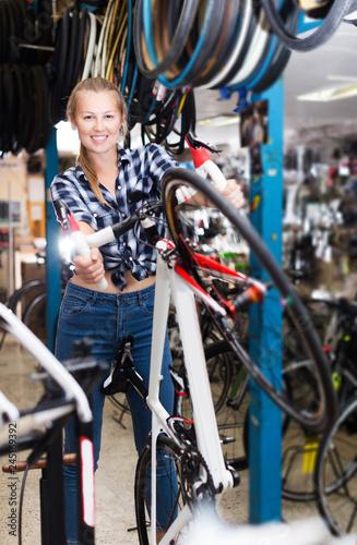 Fototapeta worker is standing near bicycle and cheking wheels obraz
