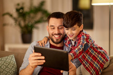 Family, Fatherhood, Technology And People Concept - Happy Father And Little Son With Tablet Pc Computer Sitting On Sofa At Home In Evening