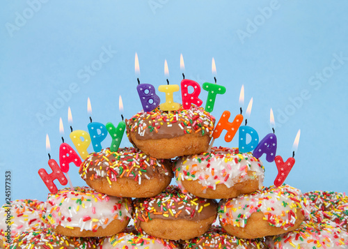 Chocolate and white frosted donuts covered in candy sprinkles piled into a cake pile with Happy Birthday candles burning brightly. Blue background.