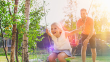 Joyous Father Pushes Swings Wi...