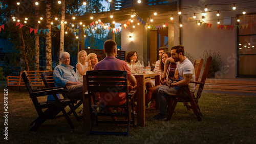 Canvas Print Sitting at the Dinner Table Handsome Young Man Plays the Guitar For a Friends