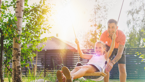 Foto  Joyous Father Pushes Swings with His Cute Little Daughter on Them