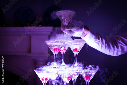 Pyramid of champagne with liquid nitrogen. Colorful lights