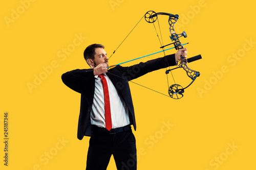 Businessman aiming at target with bow and arrow, isolated on yellow studio background Wallpaper Mural