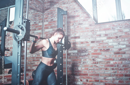 Murais de parede Athletic young woman doing lunges with the smith machine against brick walll with window at gym