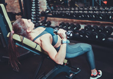Athletic Woman In Sportswear Doing A Dumbbell Press On Inclined Bench At Gym. Side View.