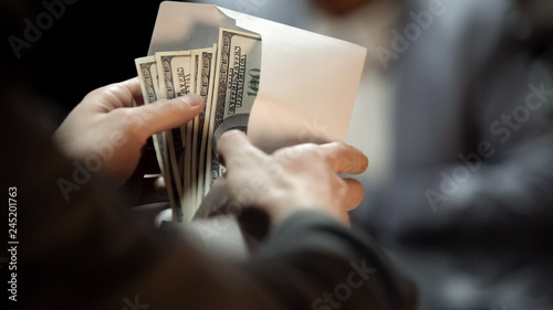 Fotografía Envelope with dollars, lady giving bribe to politician to cover illegal business