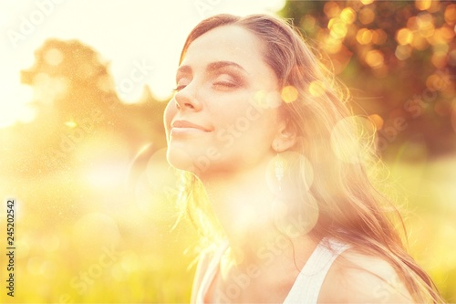 Young woman on field under sunset light Canvas Print