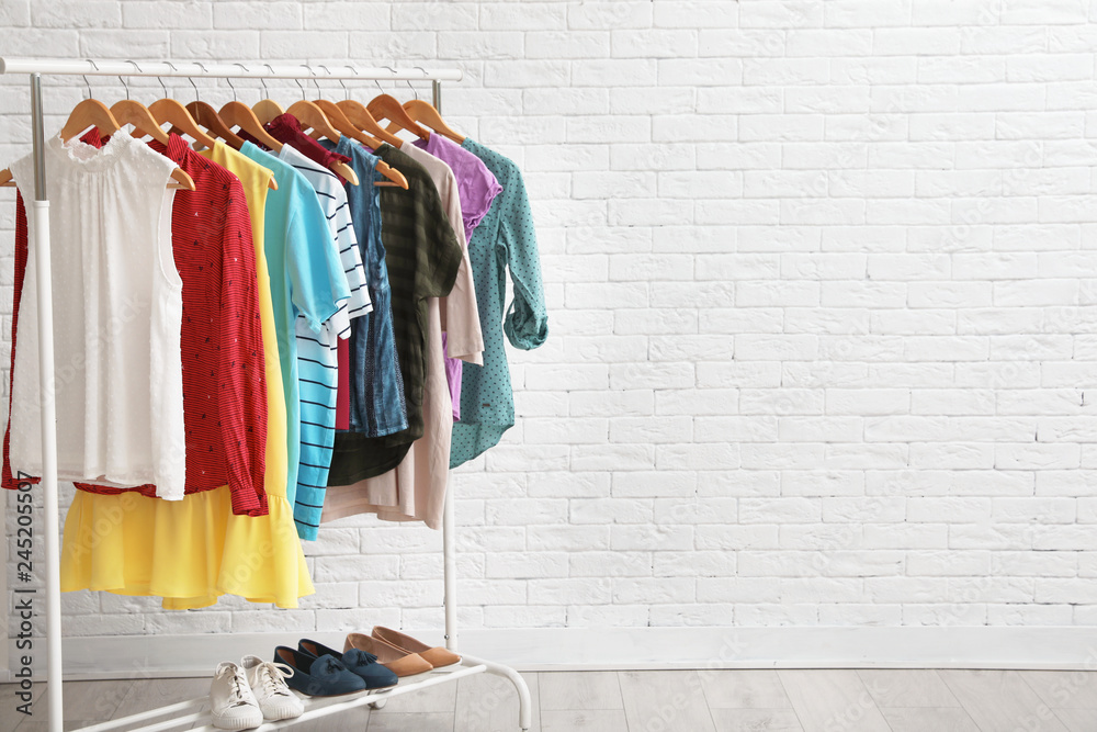 Fototapety, obrazy: Wardrobe rack with stylish clothes and shoes near brick wall indoors. Space for text