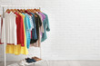 Wardrobe rack with stylish clothes and shoes near brick wall indoors. Space for text