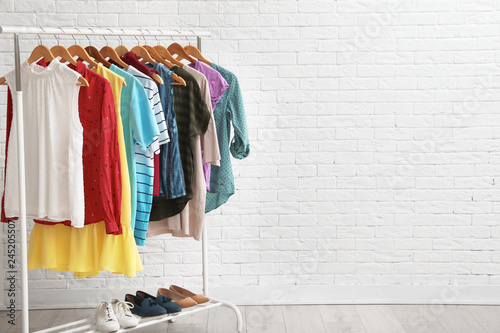 Wardrobe rack with stylish clothes and shoes near brick wall indoors. Space for text - fototapety na wymiar