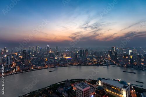 Fotobehang Aziatische Plekken Blick auf die Skyline von Shanghai am Abend: der Bund am Huangpu Fluss mit den beleuchteten Wolkenkratzern