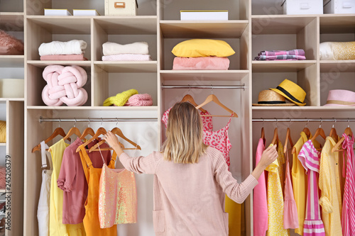 Woman choosing clothes from large wardrobe closet Fototapeta
