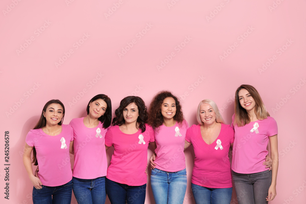 Fototapeta Group of women with silk ribbons on color background. Breast cancer awareness concept