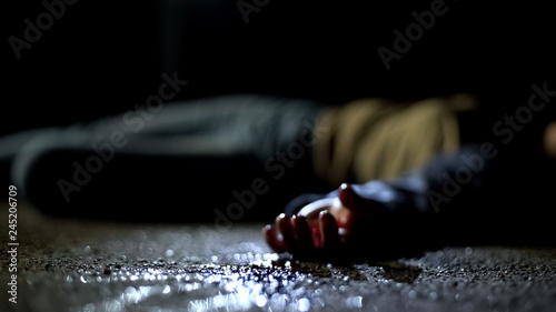 Close-up bloody body of young woman lying on ground, terrible killing, robbery Wallpaper Mural