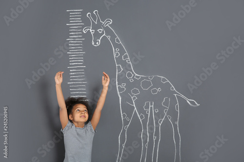 African-American child measuring height near chalk giraffe drawing on grey background