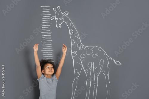 Photo African-American child measuring height near chalk giraffe drawing on grey backg
