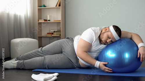 Fotografía  Obese male struggling to finish home workout program, fitness routine, goal