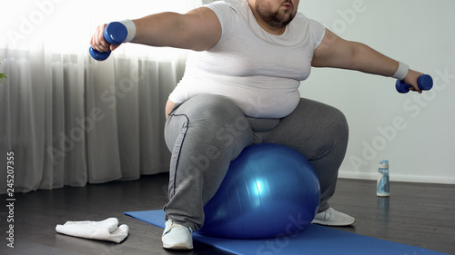 Fotografía  Corpulent male in sportswear lifting dumbbells sitting on fitness ball, activity