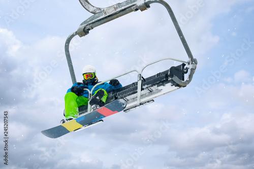 Snowboarder using ski lift at mountain resort. Winter vacation