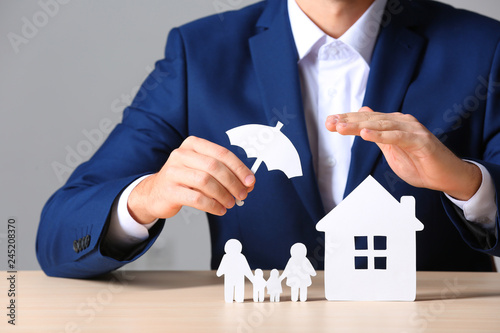Valokuva Male insurance agent covering paper family and home with umbrella cutout at tabl