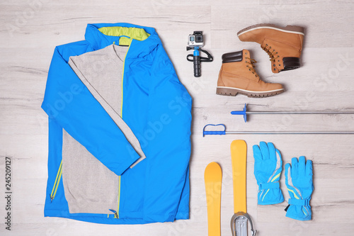 Flat lay composition with clothes, boots and skis on wooden background. Winter vacation