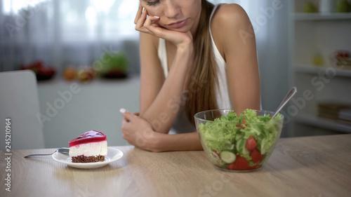 Leinwand Poster Slim female choosing between cake and salad, healthy diet vs high-calorie food