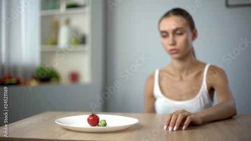Photo Exhausted slim woman looking at small portion of breakfast, self-destruction