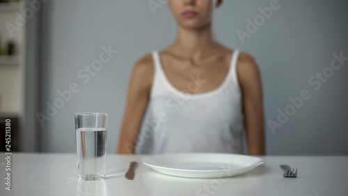 Anorexic girl sitting in front of empty plate, drinking water, severe diet Fototapeta