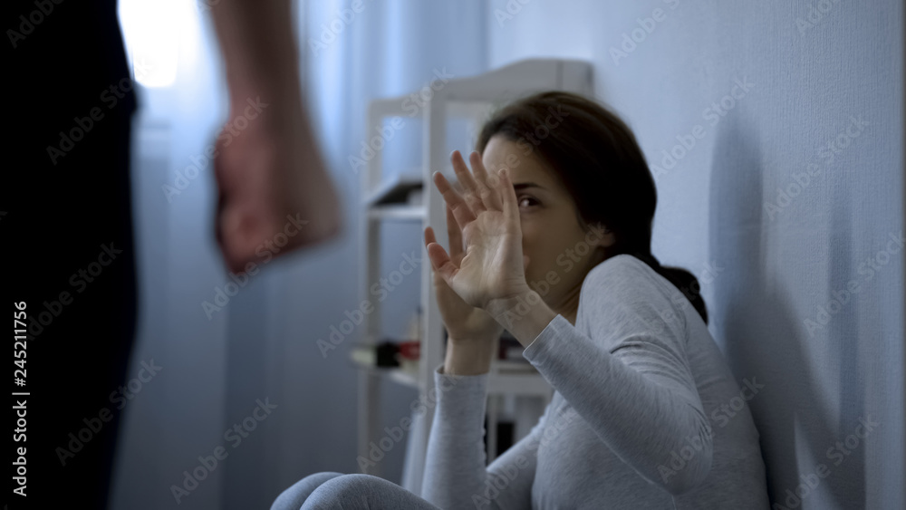 Fototapeta Woman trying to protect herself from fists of enraged husband, assault in family