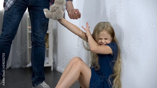 Photo  Cruel father intimidating and beating helpless little daughter assault in family