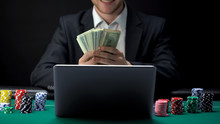 Successful Online Casino Player Counting Money In Front Of Laptop, Bet Winner