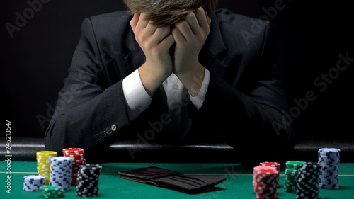 Foto Young devastated businessman losing poker game at casino, gambling addiction