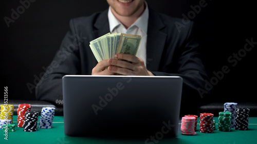 Fotografía Successful online casino player counting money in front of laptop, bet winner