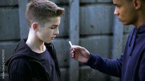 Drug dealer boy treating younger friend with marijuana cigarette, addiction Poster Mural XXL
