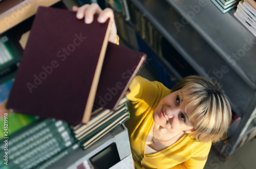 Photo Librarian woman is looking for necessary books on a bookshelf in a archive of library
