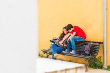 Friends Using Tablet Computer While Sitting On Bench Against Yellow Wall