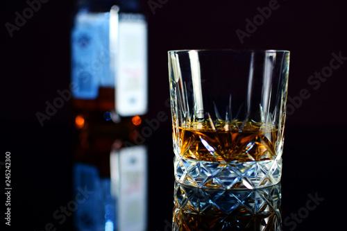 Fotomural  Whiskey in crystal glass. Bottle on background.