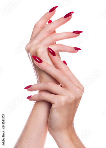 Leinwand Poster Bright festive red manicure on female hands. Nails design