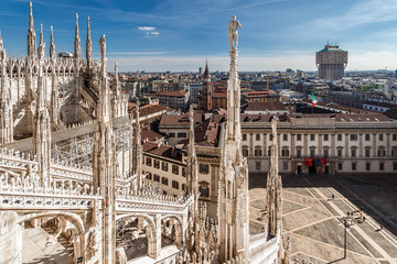 Top view from the roof of Duomo di Milano Cathedral with marble statues to the city and the Royal Palace Palazzo Reale on Piazza del Duomo square. Milan, Italy.