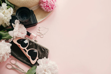 Obraz na płótnie Canvas Stylish feminine flat lay with pink peonies, hat, photo camera, retro sunglasses, jewelry and nail polish on pastel pink paper with copy space. International Women's Day. Hello spring