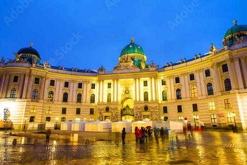 Spoed Fotobehang Wenen Illuminated Hofburg Palace seen from Michaelerplatz at night in Vienna, Austria