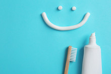 Smiling Face Made Of Toothpaste, Tube, Brush And Space For Text On Color Background, Top View