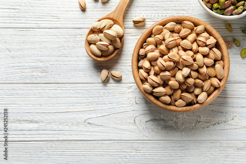 Flat lay composition with organic pistachio nuts and space for text on wooden background